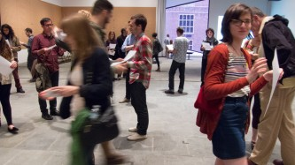 A group of people each holding a sheet of paper walk around each other