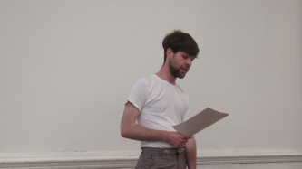Jordan Lord standing reading from a paper in a white room