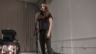 A woman standing behind a microphone in an art space