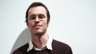 Anthony Burr wearing glasses, white shirt and jumper
