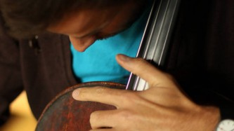 Peter Nicholson playing a cello in close up