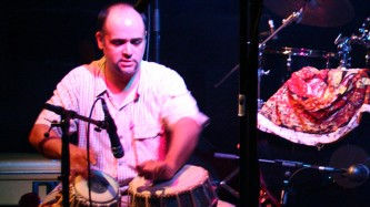 Ravi Padmanabha playing tabla near a drum kit at INSTAL 06