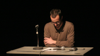 Loic sitting at a desk during a performance at UNINSTAL