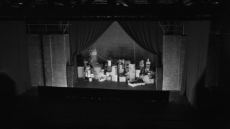 A long distance shot of a dark theatre stage piled high with cardboard boxes