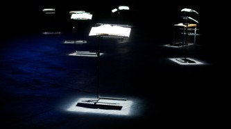 Pools of light show music stands holding large books