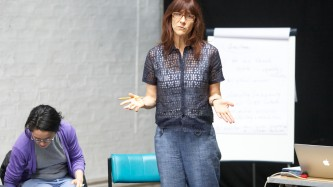 Ann Cvetkovich gesticulates as she stands and talks by a flipchart