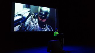 Jackie Wang reading on stage in front of a projection of Robocop