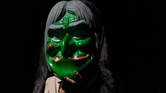 Sgaire Wood wearing a large green and grey witch mask