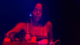 Juliana bathed in red light and wearing a strap top looks down as she DJs