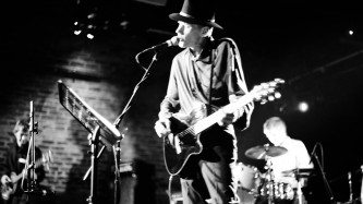 Jandek on stage wearing a hat & playing an electric guitar