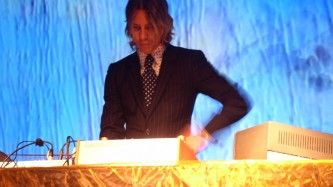 William Basinski in shirt and tie, blue screen behind, gold table to the fore