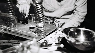 A hand reaches into a table of various objects: springs, a metal bowl, balls