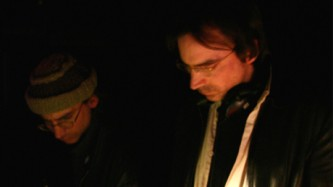 Mark and John Bain stand together looking down at some audio equipment
