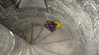 A view looking down a stone spiral staircase. A pair of trainers is on a step.