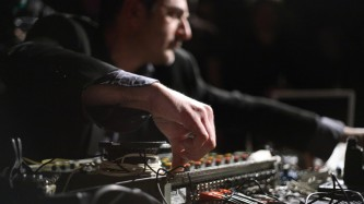 Jerome Noetinger's hand twiddling a knob on a mixing desk is in the foreground