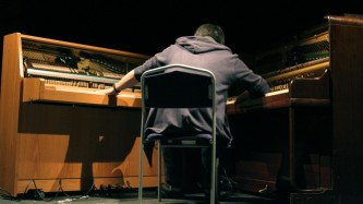 A performer in a hooded top sits between and plays two upright pianos