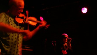 Tony conrad bowing a violin in the foreground, Keiji Haino singing behind