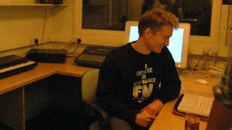 Chris Weaver smiles as he looks at a laptop in a room with screens and keyboards