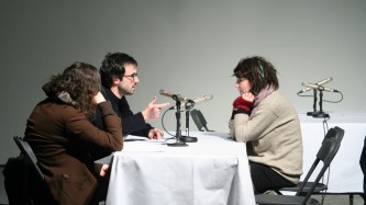 Three people sit by microphones talking
