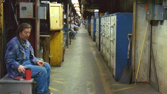 A view down a long underground corridor with lockers and a few seated figures