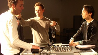 Three folks gathers around a complicated mixing desk