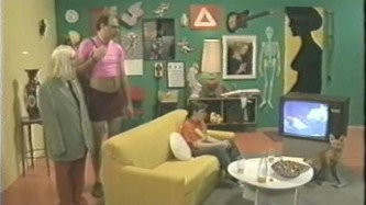 A film still of a set of a living room filled with pictures and a couple