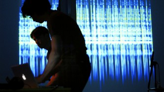 Two performers silhouetted against a projection of blue light