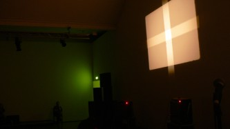 A screen showing a cross of light with some green shade in the foreground