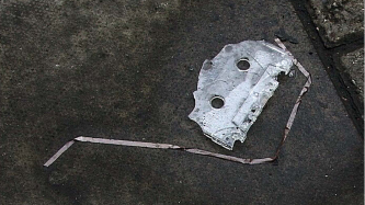 A broken c90 cassette spews a ribbon of tape onto a concrete slab