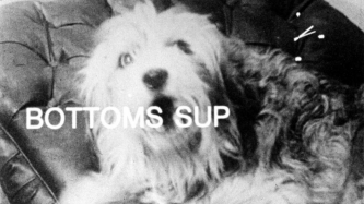 A still frame from a film. A sheepdog barks and the words Bottoms Sup are shown