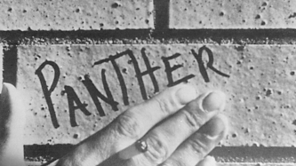 A hand frames the word Panther written on a brick in pen