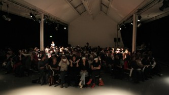 An audience seated and wearing eye masks