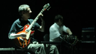 A guitarist and a drummer performing on stage
