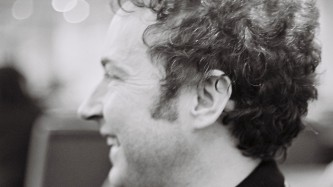 Close up profile of David Keenan smiling. He has dark wavy hair