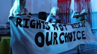 """Three people hold a banner: """"Rights Not Rescue Our Choice"""""""