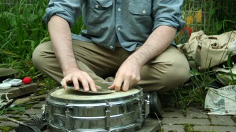 Sean Meehan sitting outdoors with a snare and cymbal