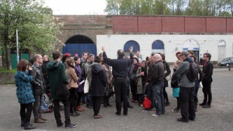 People huddled around a speaker on a street in Glasgow