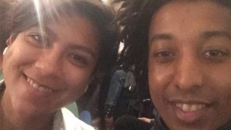 two people lean in together to grin for a selfie, the image is grainy