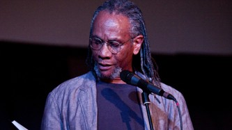 Nathaniel Mackey wearing a grey jacket and braided hair reads at a mic