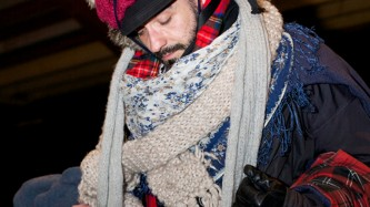 Man covered in a jumble of jumpers and scarves