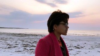 Nisha stands on a beautiful beach, wearing a textured red coat. The sky is pink.