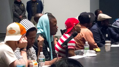 participants sit at a large table listening to the discussion