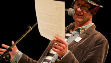 Tam Dean Burn in a hat reads from a paper into a microphone
