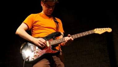 A man in an orange shirt looks down while playing a maroon guitar