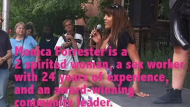 Someone sits crosslegged on a stage with a mic. Pink subtitles cover the image
