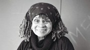 A portrait of Sonia Sanchez she is wearing a head scarf and a broad smile