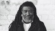 Portrait of Wadada Leo Smith in front of a white brick wall