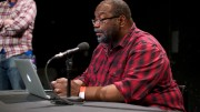 Fred Moten in a black and red shirt prepares for a discussion