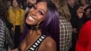 Ahya Simone with purple hair a striped top and big earring smiles hugely