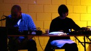Dylan and Karen sit playing electronics silhouetted in front of a yellow wall